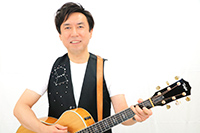 画像:ギターを弾いて歌う板橋かずゆき